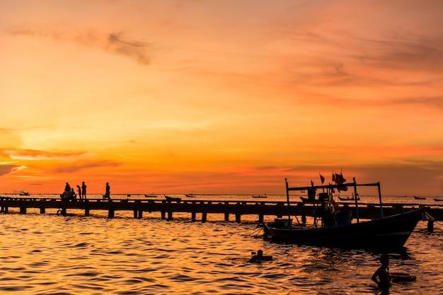 Silhueta da ponte do porto e as pessoas durante o pôr do sol na praia de bang phra, sriracha choburi, tailândia