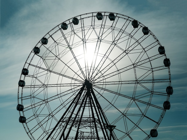 Silhueta da roda gigante de observação no parque de diversões ao fundo do céu do sol