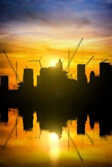 Silhueta da torre do guindaste no canteiro de obras com ondulações na reflexão da água no céu do por do sol