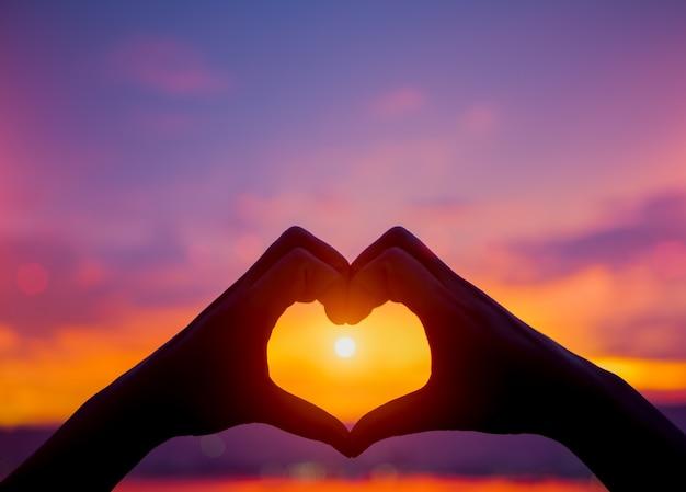 Silhueta das mãos da mulher para ser forma do coração no fundo do por do sol. amor, dia dos namorados c