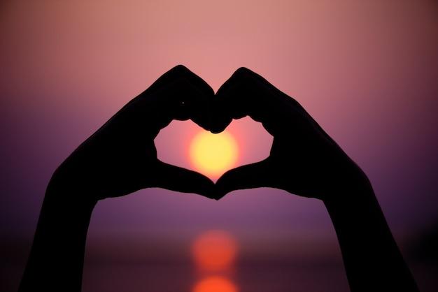 Silhueta das mãos da mulher para ser forma do coração no fundo do por do sol.