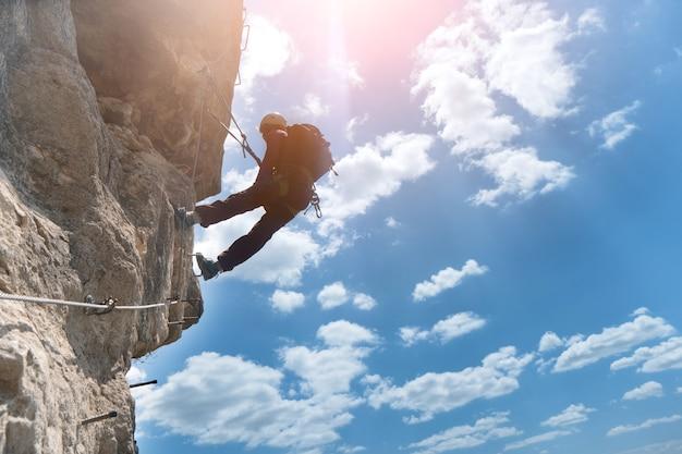 Silhueta de alpinista via ferrata escalando rocha