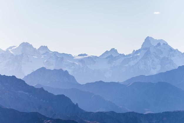 Silhueta de alta montanha em tons azul, espantosa ao pôr do sol, os alpes