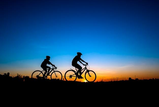 Silhueta de andar de bicicleta no fundo por do sol