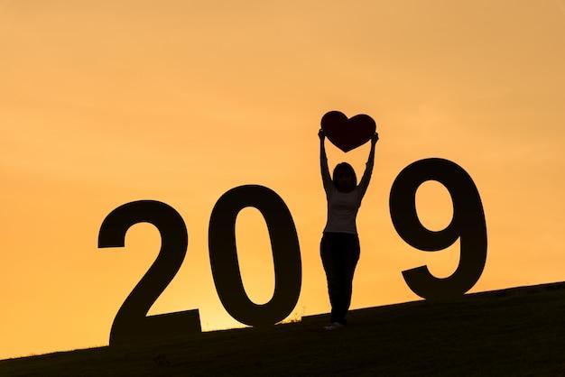 Silhueta de ano novo de 2019 da senhora asiática em pé na colina e segurando o coração
