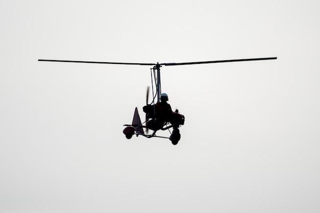 Silhueta de autogiro voando em fundo branco.