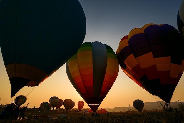 Silhueta de balão de ar quente sobre a paisagem do lago de montanhas ao pôr do sol