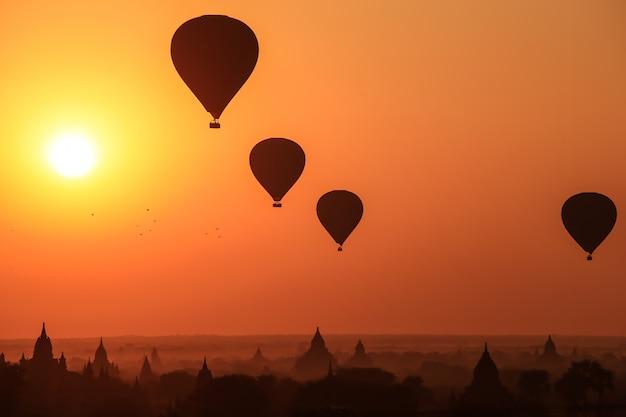 Silhueta de balão de ar quente sobre bagan ao nascer do sol na manhã nublada, myanmar