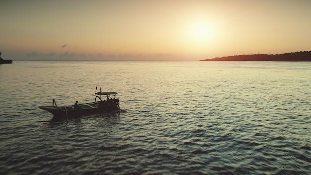 Silhueta de barcos de pesca com drones aéreos na bela paisagem do pôr do sol do oceano em bali tropical