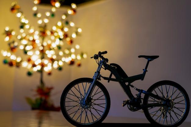 Silhueta de bicicleta em miniatura e árvore de natal turva no fundo.