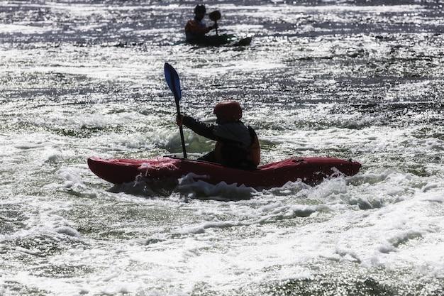 Silhueta de caiaque masculino ativo em águas agitadas