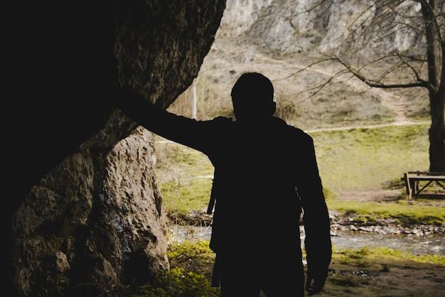 Silhueta de caminhante em uma caverna