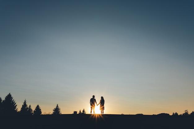 Silhueta de casais que de mãos dadas sobe a colina