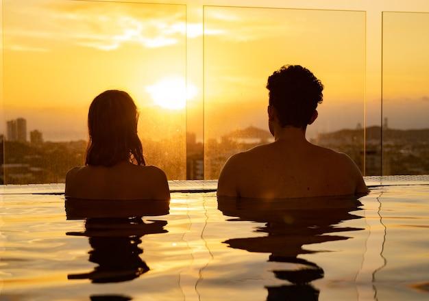 Silhueta de casal apaixonado na água do pólo infinito durante o pôr do sol. conceito de férias românticas.