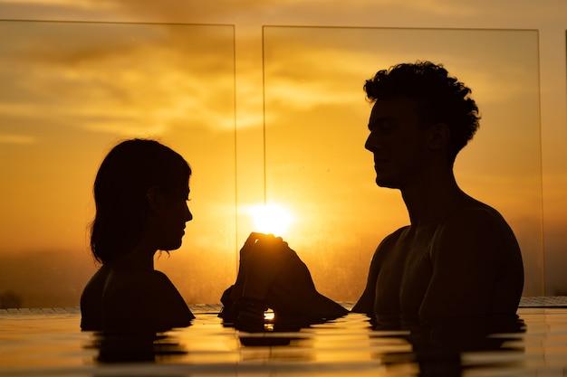Silhueta de casal apaixonado na água do pólo infinito durante o pôr do sol. romance e relacionamento