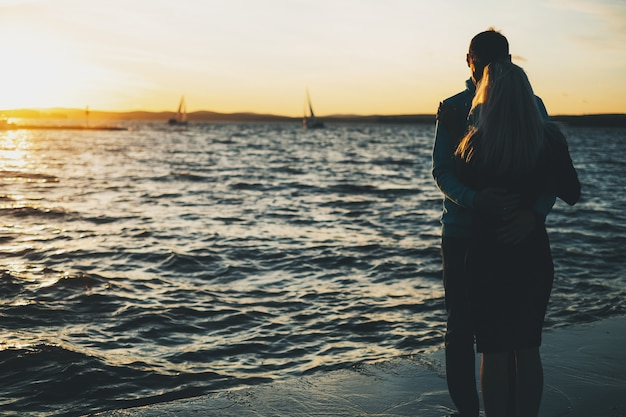 Silhueta de casal apaixonado no cais, tempo do sol, veleiros