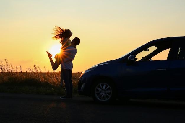 Silhueta de casal feliz perto de seu carro novo na zona rural ao pôr do sol