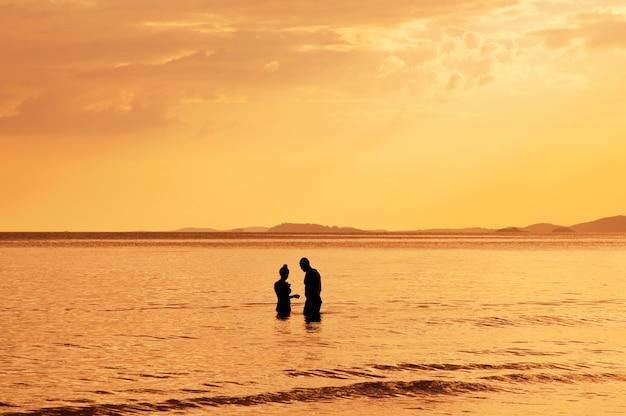 Silhueta de casal no mar ao pôr do sol