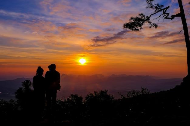 Silhueta de casal no topo de uma montanha ao pôr do sol