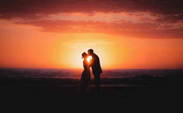 Silhueta de casal, noiva e noivo segurando a mão durante a hora do nascer do sol na praia