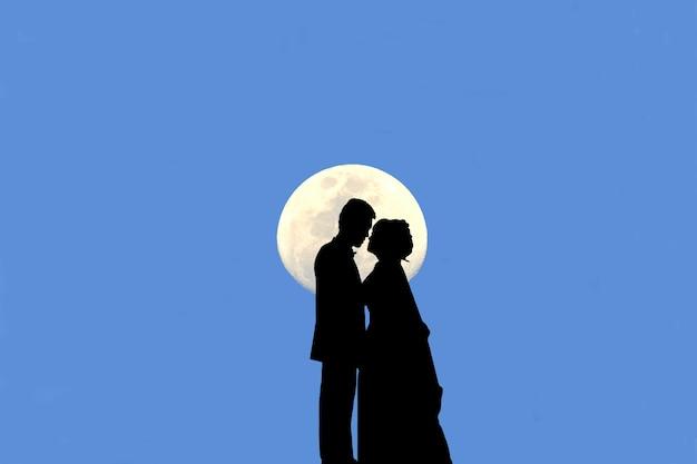 Silhueta de casal se beijando há uma lua e o céu azul é o fundo.