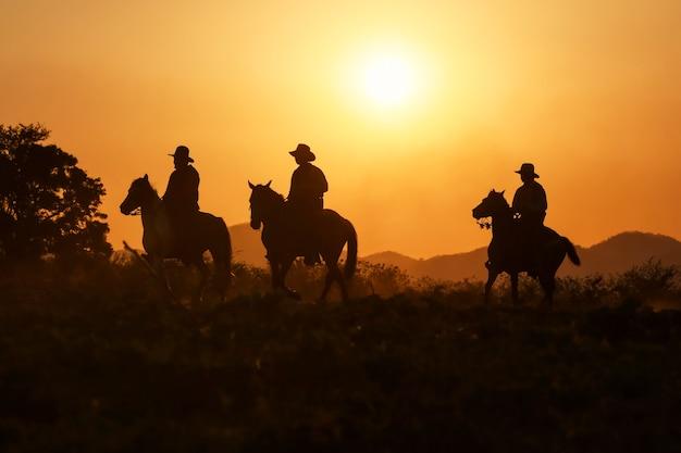 Silhueta de caubói cavalgando quando o pôr do sol está lindo
