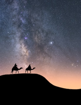 Silhueta de cavaleiros em seus camelos no deserto à noite