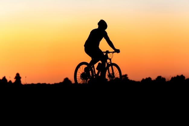 Silhueta de ciclista em movimento no fundo do belo pôr do sol