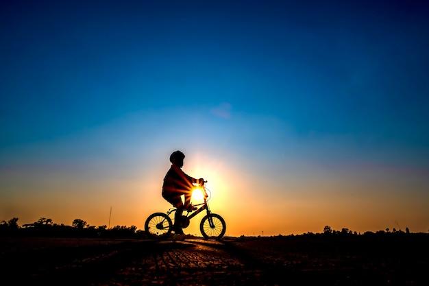 Silhueta de ciclista no fundo por do sol.