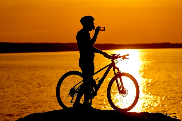 Silhueta de ciclistas ao pôr do sol. o homem está bebendo água. rio ao fundo. conceito de estilo de vida.