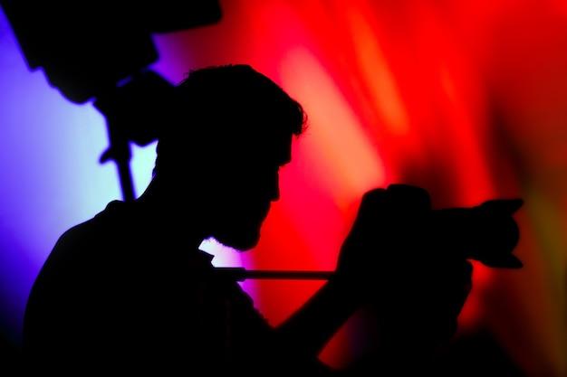 Silhueta de cinegrafista de homem com câmera de vídeo no evento
