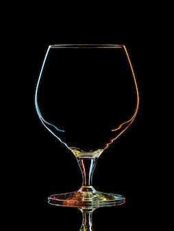 Silhueta de copo de uísque colorido com traçado de recorte em fundo preto.