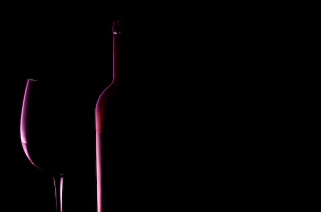 Silhueta de copo de vinho tinto e garrafa fundo preto lugar para texto reflexo rosa