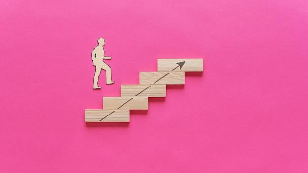 Silhueta de corte de papel de um empresário subindo as escadas feitas de pinos de madeira com uma seta apontando para cima.