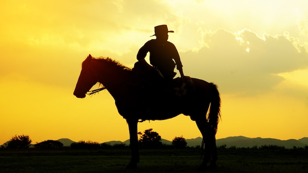 Silhueta de cowboy cavalo contra o pôr do sol no campo