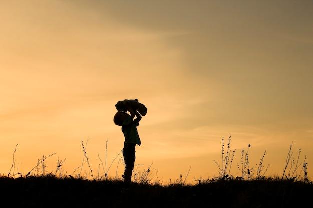 Silhueta de criança brincar com urso no pôr do sol