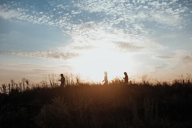 Silhueta de crianças correndo pelo campo ao pôr do sol