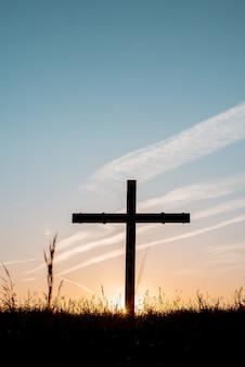Silhueta de cruz de madeira em um campo gramado com um céu azul ao fundo em um tiro vertical