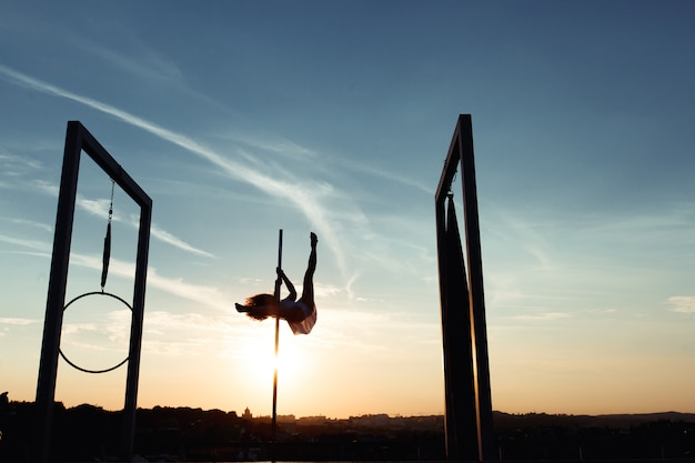 Silhueta de dançarina sexy do poste que executa no telhado no por do sol