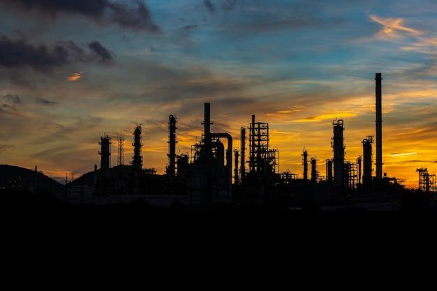 Silhueta de destilação de gás de torre de planta de refinaria de óleo de tanque e óleo de tanque de coluna da indústria petroquímica no fundo do céu ao pôr do sol