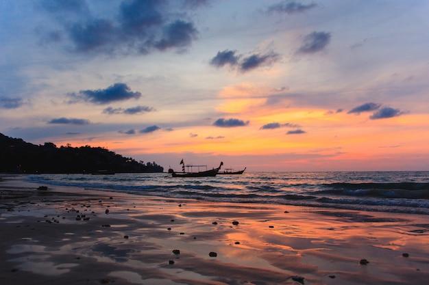 Silhueta de dois barcos tradicionais do longtail na maré baixa no por do sol na praia de kamala em tailândia.