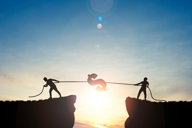 Silhueta de dois homens puxando o cifrão na colina com o céu azul no nascer do sol.
