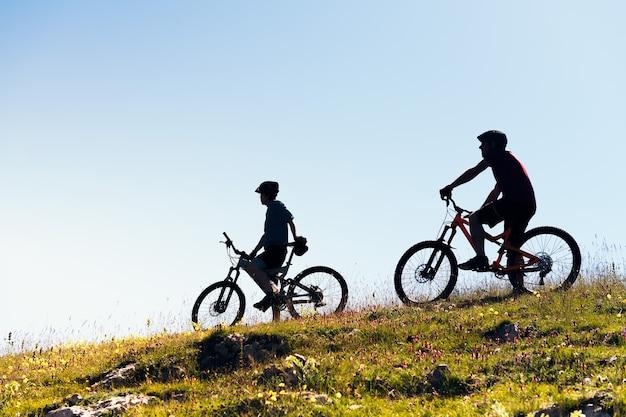 Silhueta de dois jovens com bicicletas de montanha