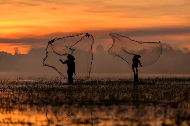 Silhueta de dois pescadores pescando com uma rede ao pôr do sol.