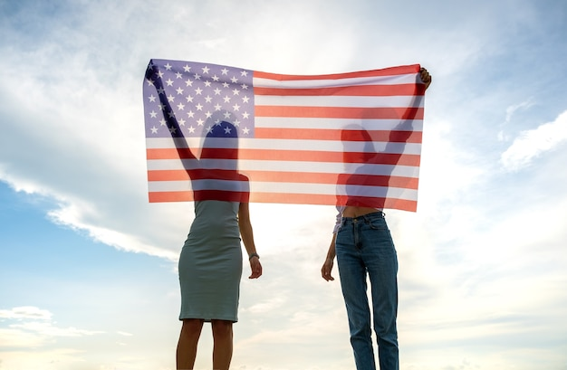 Silhueta de duas mulheres de amigos jovens segurando a bandeira nacional dos eua nas mãos ao pôr do sol. garotas patrióticas comemorando o dia da independência dos estados unidos. dia internacional do conceito de democracia.