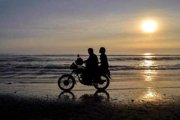 Silhueta de duas pessoas em uma motocicleta no fundo uma praia ao pôr do sol