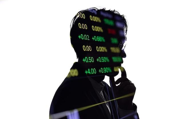 Silhueta de exposição dupla do empresário pensando com a lista de preços do mercado de ações. conceito de negócios e economia financeira.
