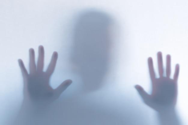 Silhueta de fantasma assustador desfocado atrás de um copo branco