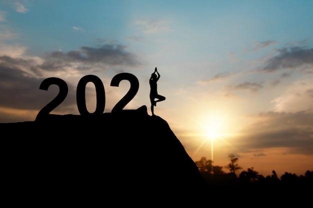 Silhueta de feliz ano novo 2021 com mulher fazendo yoga