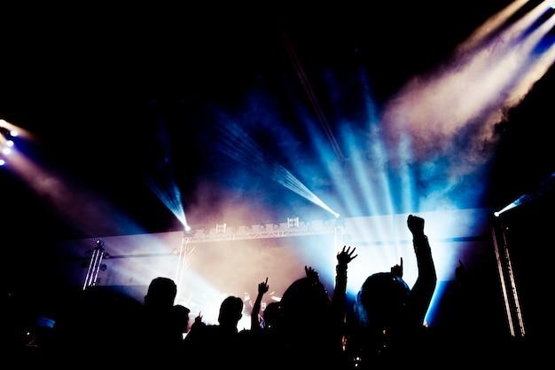 Silhueta de festa de concerto abstrata com luz e fumaça no momento feliz
